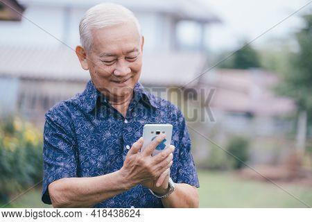 Happy Asian Elder Man Using Smartphone.