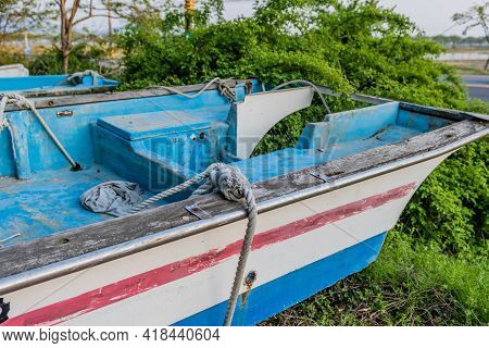 Fishing Boats On Grassy Mound Beside Row Of Tress