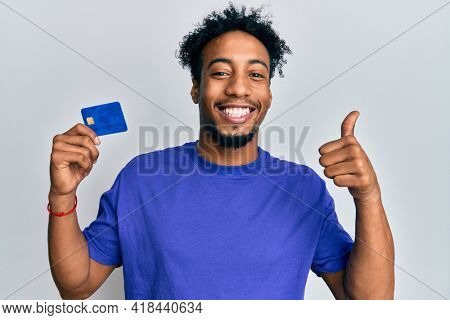 Young african american man with beard holding credit card smiling happy and positive, thumb up doing excellent and approval sign