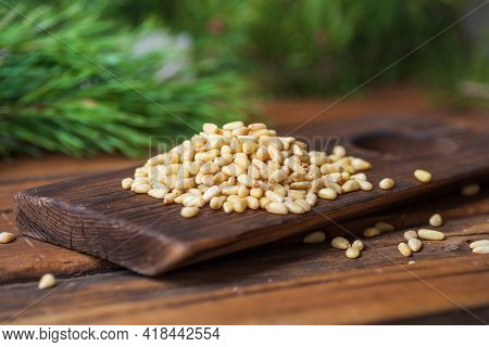 Peeled Pine Nuts Are Heaped On A Dark Wooden Cutting Board. In The Background, Sprawling Branches Of