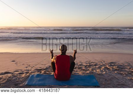 Rear view of senior african american man meditating and practicing yoga while sitting on yoga mat at the beach. fitness yoga and healthy lifestyle concept