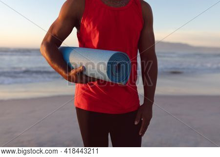 Mid section of senior african american man holding yoga mat at the beach. fitness yoga and healthy lifestyle concept