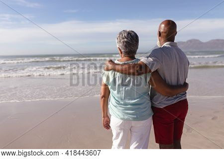 Rear view of senior african american couple hugging each other on the beach. travel vacation retirement lifestyle concept