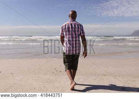 Rear view of senior african american man walking on the beach. travel vacation retirement lifestyle concept