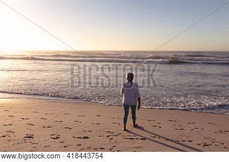 Rear view of senior african american woman walking on the beach. travel vacation retirement lifestyle concept