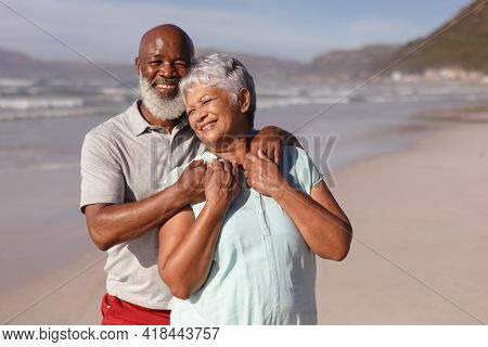Happy senior african american couple embracing each other on the beach. travel vacation retirement lifestyle concept