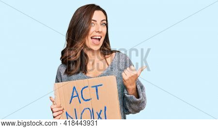Young brunette woman holding act now banner pointing thumb up to the side smiling happy with open mouth