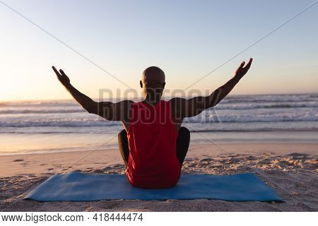 Rear view of senior african american man with arms wide open practicing yoga at the beach. fitness yoga and healthy lifestyle concept