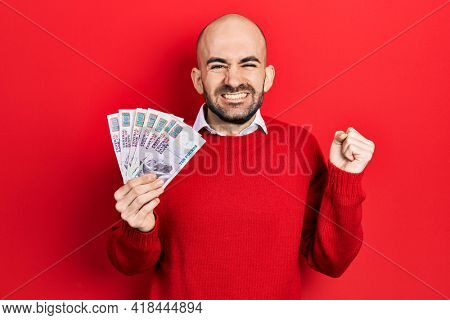 Young bald man holding egyptian pounds banknotes screaming proud, celebrating victory and success very excited with raised arm