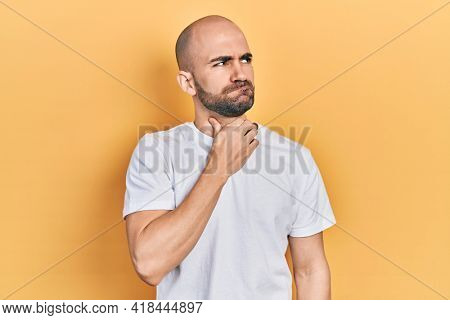 Young bald man wearing casual white t shirt touching painful neck, sore throat for flu, clod and infection