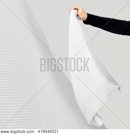 Woman's hand holding white pleated scarf fashion studio shoot