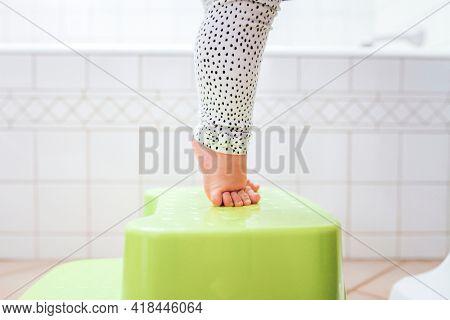 Toddler's bare feet tiptoeing on the stool