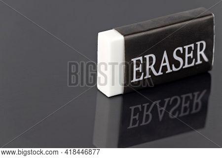 black and white eraser with reflection on dark background