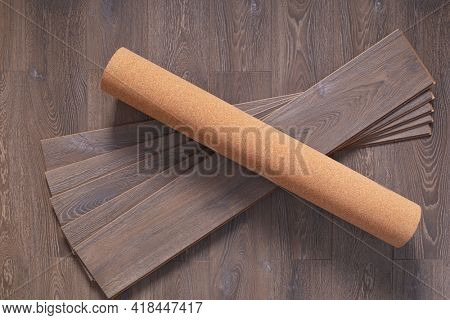 Cork roll and laminate floor wood background texture. Wooden laminate floor plank with copy space