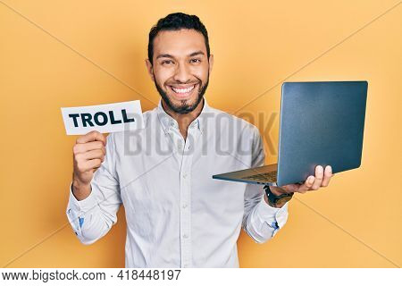 Hispanic man with beard working using computer laptop holding banner with troll word smiling with a happy and cool smile on face. showing teeth.