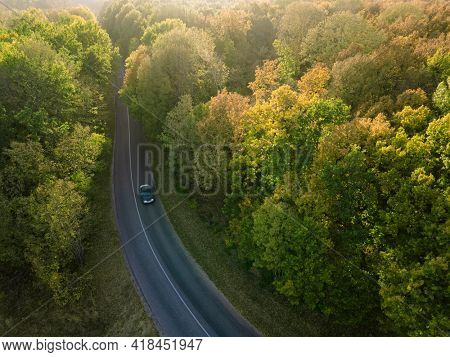 Aerial view on Highway road in the forest. View from a drone. Car in summer time nature from air. Aerial view.