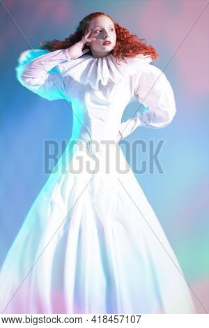 Sophisticated female model with lush red curly hair posing in a white art dress with collar. A studio portrait with mixed color lighting in haze. Fashion art.