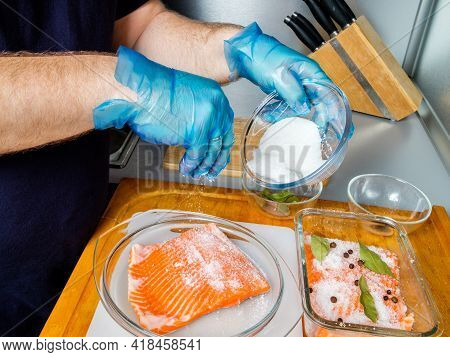 The Hands Of The Cook In Hygienic Gloves Sprinkle Salmon Fillets With Curing Mixture. The Process Of
