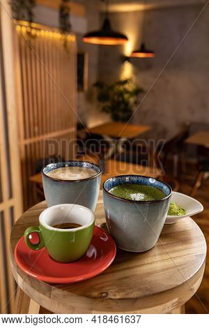 Cups Of Coffee, Espresso And Matcha Latte On Table At A Cafe Blurred Background