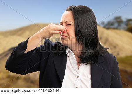 Female Entrepreneur Businesswoman Wearing Suit At Construction Site Making Bad Smell Gesture Holding