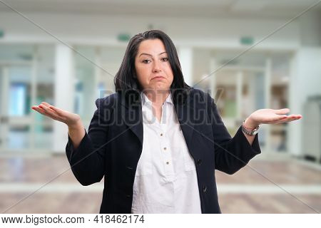 Confused Businesswoman Wearing Smart Casual Office Suit Making Shrug Question Gesture With Curious E