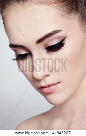 Close-up portrait of young beautiful girl with cat eye make-up
