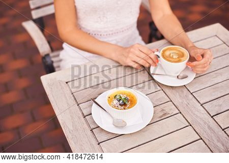 Woman Drink Delicious Caffeine Drink Aroma Latte With French Dessert Of Custard Topped With Carameli