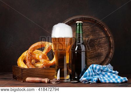 Lager beer with homemade pretzels and old wooden beer barrel. With copy space