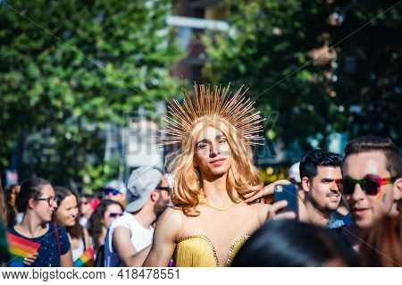 Barcelona - Spain. June 29, 2019: Sophisticated young crossdresser with black eyebrows, a wig of white hair and a halo