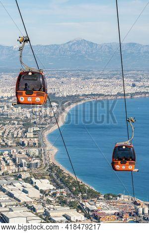 Antalya, Turkey - November 26, 2020: Cable car Teleferik to Tunektepe mountain in Antalya, Turkey. Cable car cabins with Antalya cityscape, Konyyalti beach and Mediterranean sea at background.