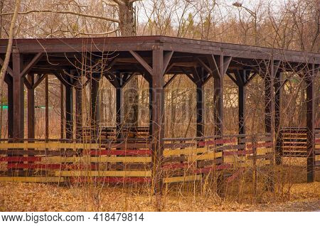 lit old wooden gazebo in the park with colorful foliage and forest in the background during sunny autumn day