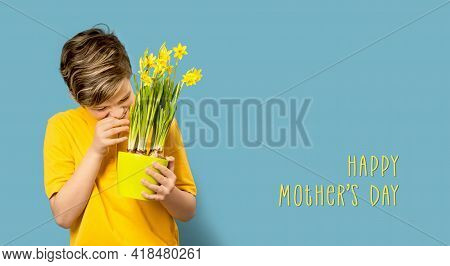 Smiling Boy Hiding Behind Daffodils. Mother's Day Card On Blue