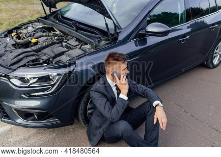 Businessman Calling For Roadside Assistance. Upset Young Man Use Phone Sitting On Road Near The Brok