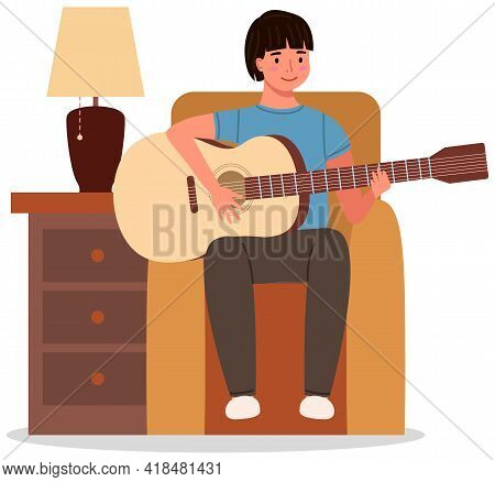 Young Man Playing Guitar At Home. Private Guitar Lessons. Guy Sitting On Armchair With Musical Instr