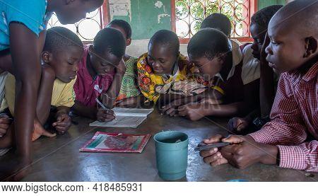 Mzuzu, Malawi. 30-05-2018. Group Of African Children Reunited Inside Their Classroom Working On An E