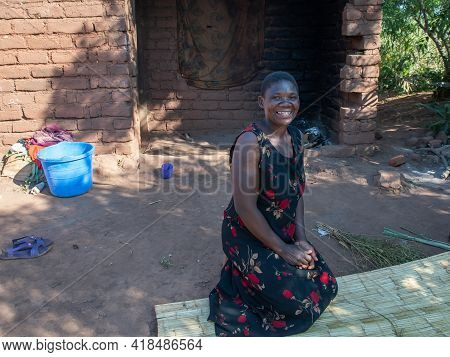 Mzuzu, Malawi. 30-05-2018. Happy Afro-descendent Mother Smiling At The Camera In Front Of Her House