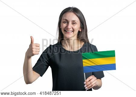 Happy Young White Woman Holding Flag Of Gabon And Shows The Class By Hand Isolated On A White Backgr