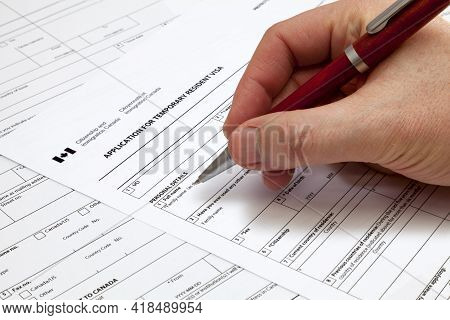 A Man Holding A Ballpoint Pen To Fill A Permanent Residence Visa Application Form To Canada.