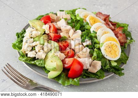healthy American Cobb salad with egg bacon avocado chicken tomato. hearty keto low carb diet