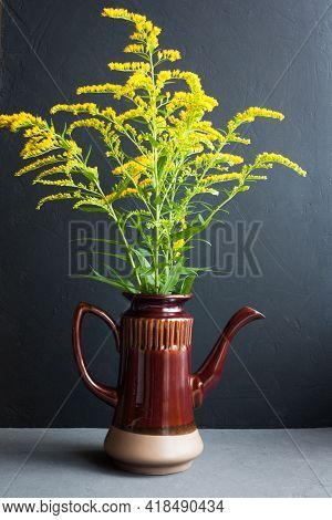 Bouquet Of Canadian Goldenrod In A Brown Ceramic Teapot On A Gray Background, Twigs With Delicate Ye