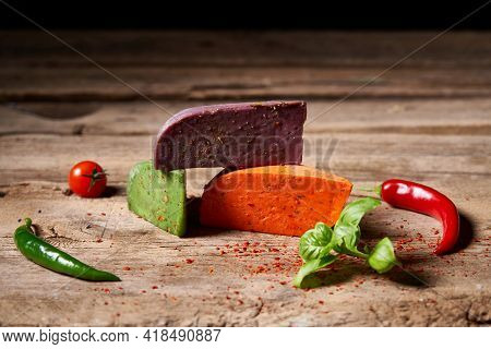 Three Different Colored Gourmet Cheeses Lying On Rough Wooden Planks With Vegetables, Copy Space Abo