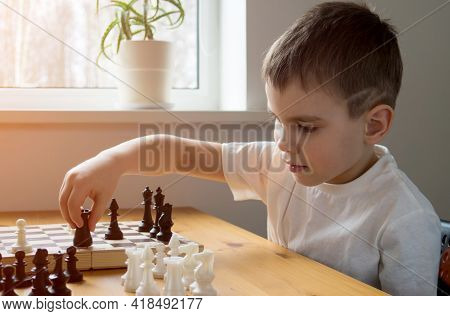 A Preschool Boy Arranges Pieces On A Chessboard For Playing Chess. Board Games.