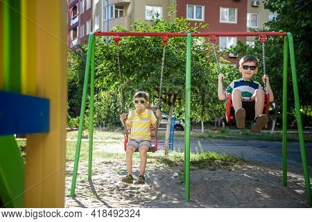 Two Little Kid Boys Having Fun With Swing On Outdoor Playground.