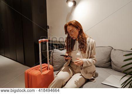 Young Businesswoman Work At Hotel. Business Trip Concept. Very Busy Red-haired Female Model In Styli