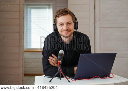 Portrait Of Influencer Podcast Creator Streaming Audio Broadcast At His Home. Broadcasting An Interv