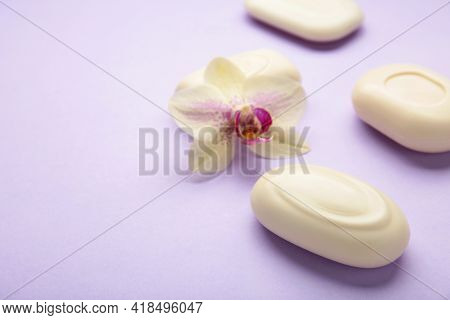 Different White Soaps With Flowers. A Lot Of Solid Soap For Hygiene And Cleanliness On Purple Backgr