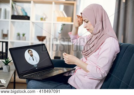 Stay At Home Concept. Covid Prevention. Ill Muslim Woman Sitting On Sofa At Home, Feeling Bad And Ha