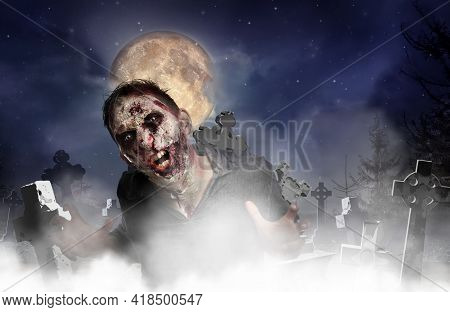Scary Zombie At Misty Cemetery Under Full Moon. Halloween Monster