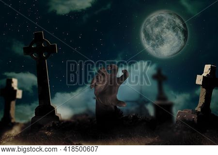Scary Zombie Rising Out Of Grave At Misty Cemetery Under Full Moon. Halloween Monster