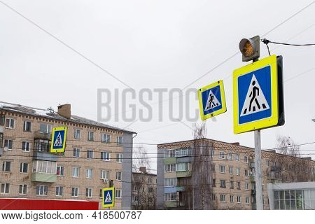 Road Signs Man In A Blue Square, Means A Pedestrian Crossing. The Yellow Traffic Light Warning Light